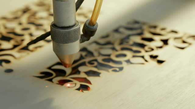 stockvideo's en b-roll-footage met machine voor laser snijden hout dicht bezuinigingen spaanplaat en de rook wordt weergegeven. de rode balk - laser