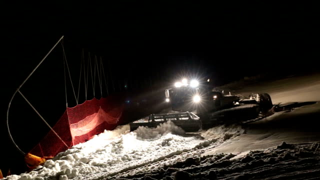 Machine for leveling the ski slopes works at night. video