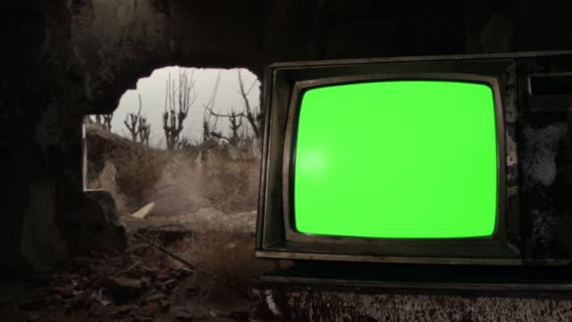 vidéos et rushes de tir de mitrailleuse au-dessus de l'écran vert rétro de tv dans un bâtiment démoli dans la zone de guerre. - mitrailleuse