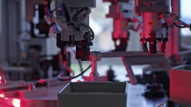 vidéos et rushes de machine de ld dans l'usine ramassant des pièces en plastique outre du plateau mécanisé et les triant - machinerie