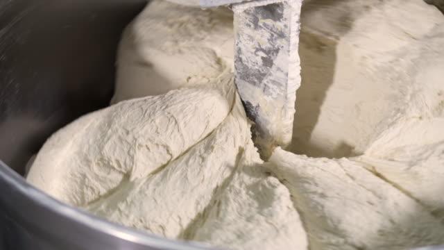 vidéos et rushes de machine pétrir la pâte de farine production usine pain plante pain frais pain cuit au four brioche boulangerie alimentaire production d'usine avec des produits frais - batteur électrique