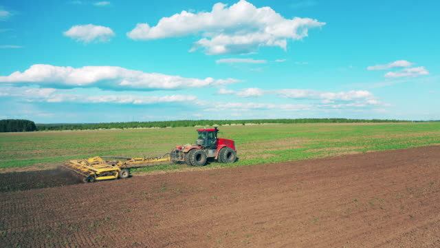 A machine sows soil on a big field. A machine sows soil on a big field. 4K agricultural occupation stock videos & royalty-free footage