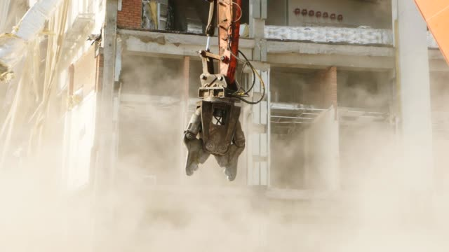machine with large metal scissors in dust at demolition site
