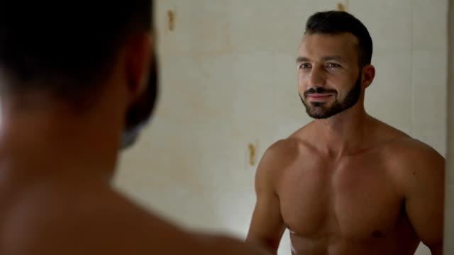 マッチョな男は、ジムでのエクササイズを準備、脇の下に制汗剤を適用します。 - 体 洗う点の映像素材/bロール