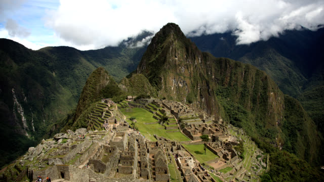 Machu and Wayna Picchu Timelapse wide shot looking towards wayna picchu from machu picchu.  Tourists crawl like ants over the surface far away and clouds, mist and shadows move in timelapse archaeology stock videos & royalty-free footage