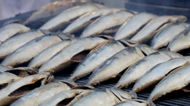 Mackerel hot smoked. Carcasses of fish in grill from which there is a light smoke video