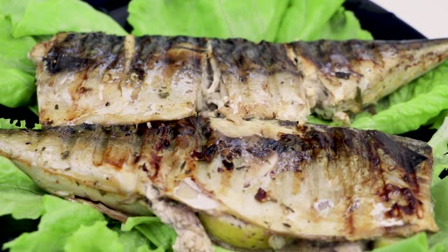 vídeos de stock e filmes b-roll de mackerel is roasted on an electric grill. grilled fish with lemon and salad - assado no forno