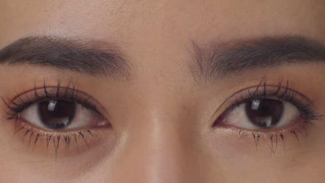 Macro Close up shot on eye of young asian woman with natural makeup in slow motion.
