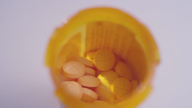 makro närbild av en flaska full av amfetamin/dextroamfetamin piller spinning på en vit yta - amfetamin pills bildbanksvideor och videomaterial från bakom kulisserna