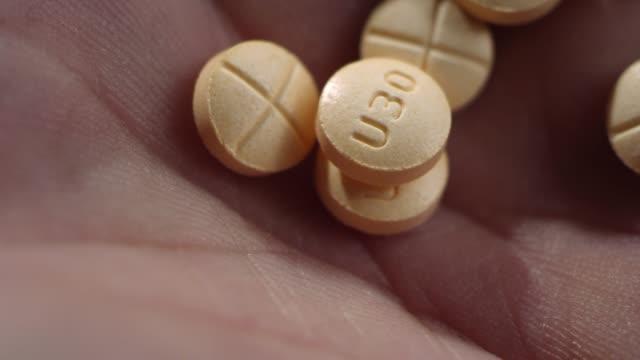 makro närbild av amfetamin/dextroamfetamin piller sjunker i en mänsklig hand - amfetamin pills bildbanksvideor och videomaterial från bakom kulisserna