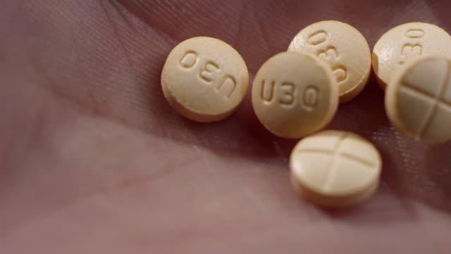 stockvideo's en b-roll-footage met macro close-up van amfetamine/dextroamfetamine pillen in een menselijke hand - amfetamine