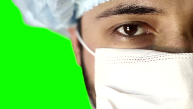 macro close-up of human eye. a man in a medical mask and cap. - веко стоковые видео и кадры b-roll