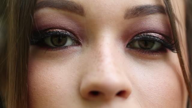 Macro closeup of pretty girl eyes looking to camera. young woman opening and closing eyes