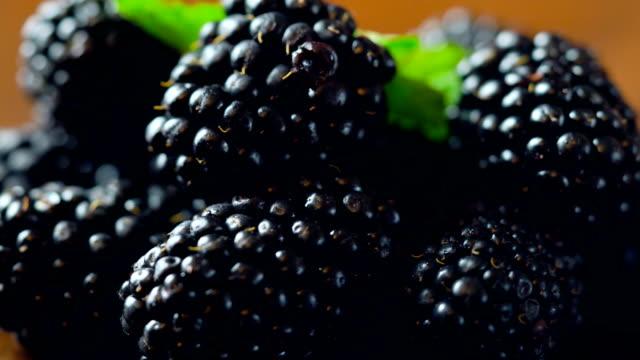 Macro closeup of rotating summer fruit blackberries on wooden table.