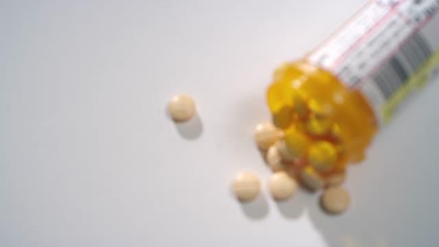 makro närbild rack fokus för ett piller flaska amfetamin/dextroamfetamin piller utspridda på en vit yta - amfetamin pills bildbanksvideor och videomaterial från bakom kulisserna