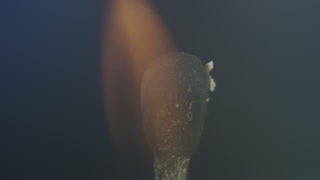 vídeos de stock e filmes b-roll de macro close-up shot of burning match with black background - inflamável