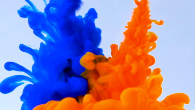 Macro concept of multicolored inks falling and mixing in water abstract background video