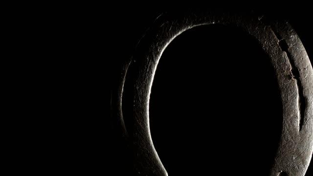 macro dolly: horseshoe on black background - horseshoe stock videos & royalty-free footage