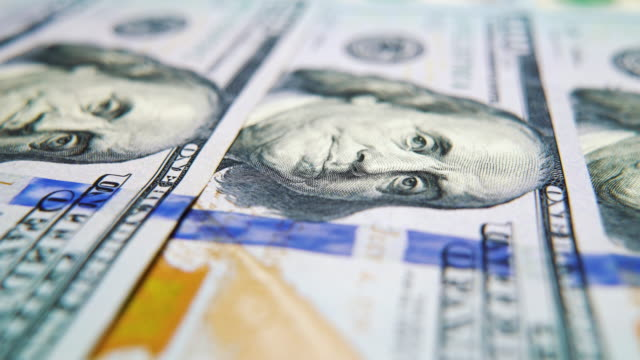 Macro dolly shot of American hundred dollar bills lying in row video