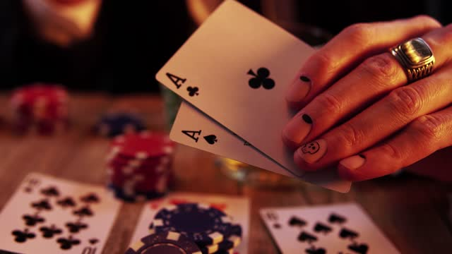 Macro footage of a hand with manicure holding two aces in process of playing poker