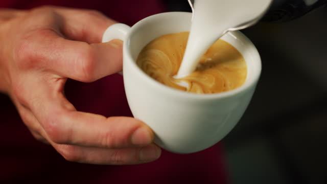 makro eines barmanns, während sie einen cappuccino neben der kaffeemaschine in einer typisch italienischen bar machen. - milchkaffee stock-videos und b-roll-filmmaterial