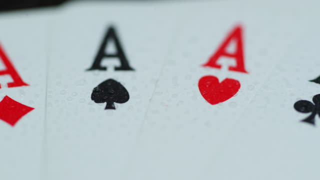 Macro of a shot of playing cards with all four aces hearths diamonds space cross lying on an elephant while moving when the cards are splashed with water leaving a drop of detail.
