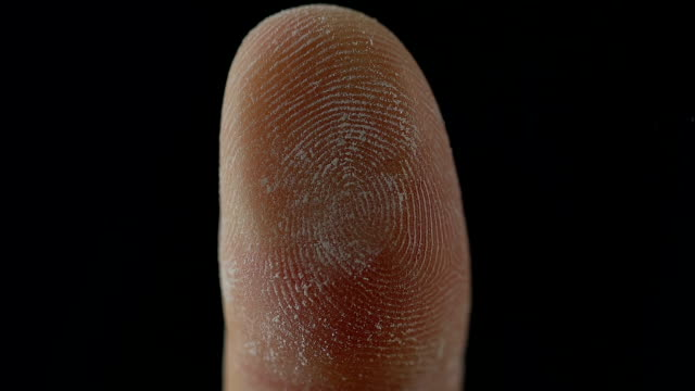 Macro of fingerprint leaning on control glass for biometric scan, technologies