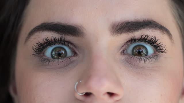 vídeos de stock, filmes e b-roll de macro de olhos verdes, abrindo com uma expressão de surpresa e choque - largo descrição geral