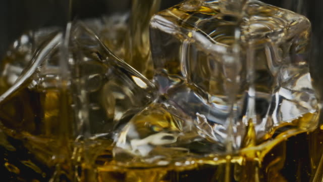 macro of whiskey pouring in glass with ice cubes in slow motion. alcohol pouring - scotch whisky video stock e b–roll