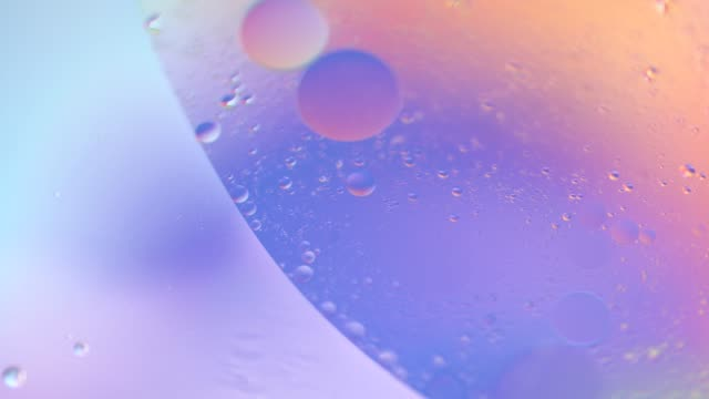 Macro oil drop in water. Pink, purple, pastel neon color bubbles. Real holographic liquid