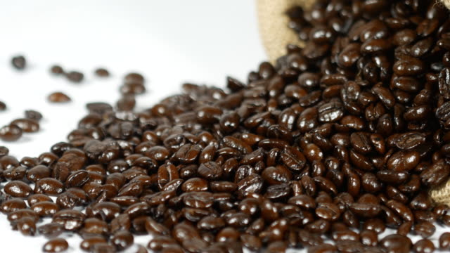 Macro panning shot of coffee beans in sackcloth on the table video