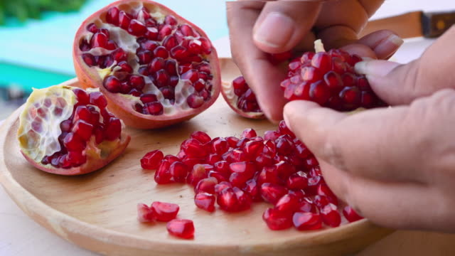 vídeos de stock e filmes b-roll de macro rotate video of seeds of a pomegranate that is red like a ruby that can be eaten - romã