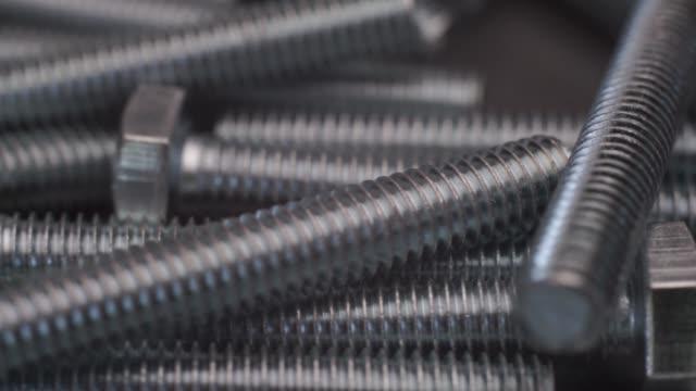 macro screws rotating on a metal table and black background. seamless loop. - затягивание стоковые видео и кадры b-roll