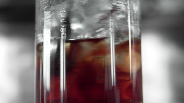macro shoot of glass full with a ice cubes and red alcohols mixing with a barman cocktails spoon. martini in a glass with a ice. making of cocktails. negroni. - rum superalcolico video stock e b–roll