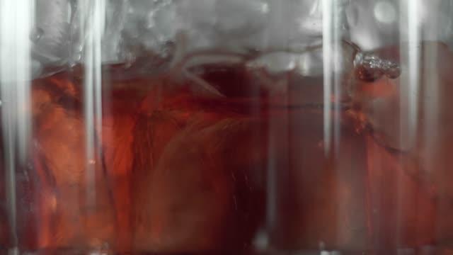 stockvideo's en b-roll-footage met macro opnamen van rode martini gieten in een glas vol met een ijsblokjes. martini vult een glas met ijs. het maken van cocktails. negroni. - martini