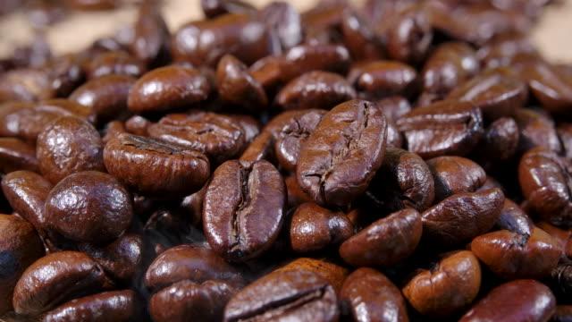 makro schoss dunkle kaffeebohne mit rauch - rohe kaffeebohne stock-videos und b-roll-filmmaterial