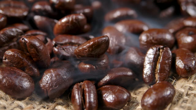 macro shot dark coffee bean with smoke - ritemprarsi video stock e b–roll