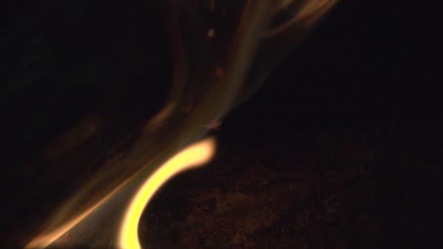 colpo macro di una fiamma al rallentatore che brucia un tronco in una stufa a legna. - tizzone video stock e b–roll
