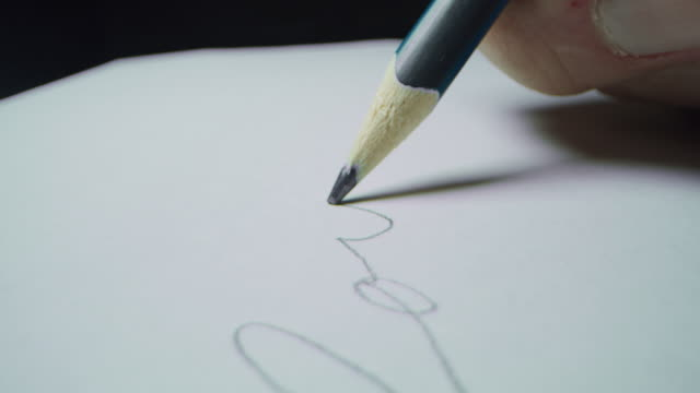 Macro shot of a hand writing a word in pencil.