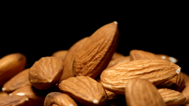 vídeos de stock e filmes b-roll de slow motion: macro shot of falling of almond on a heap - amendoas