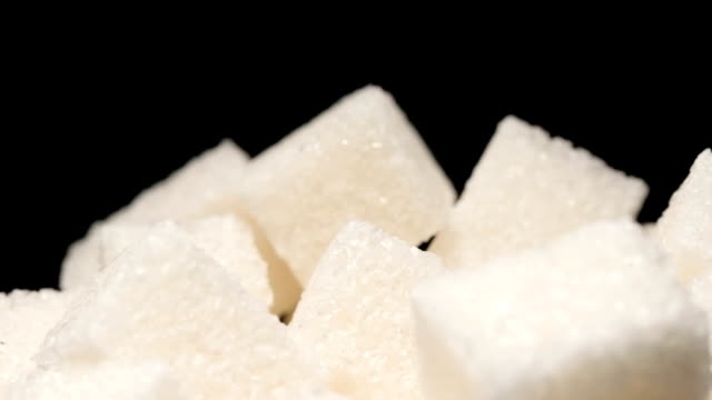 slow motion: macro shot of falling of sugar cube on a heap - chef triste video stock e b–roll