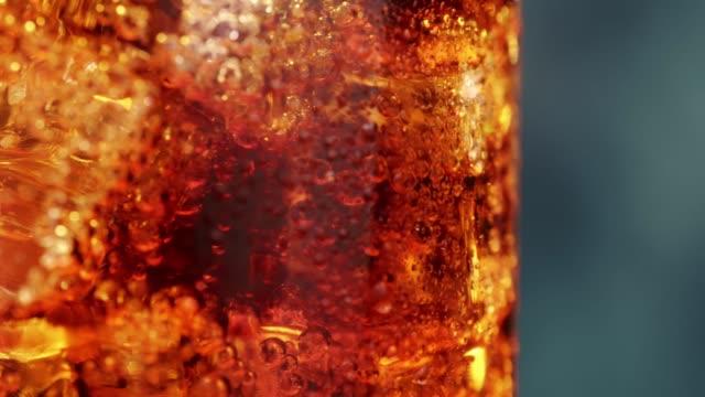 vídeos de stock e filmes b-roll de macro shot of glass with ice cubes and bubbles of carbonated cola soda drink, close up - bebida fresca