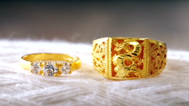 Macro shot of golden wedding rings with white textured background. Macro shot and selective focus with color grading. Use for background clip or insert shot : Macro shot of golden wedding rings with white textured background. brushed metal stock videos & royalty-free footage