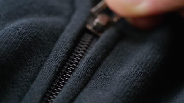Macro shot of Hand zipped on cloth ECU Macro shot of Hand zipped on cloth fabric swatch stock videos & royalty-free footage