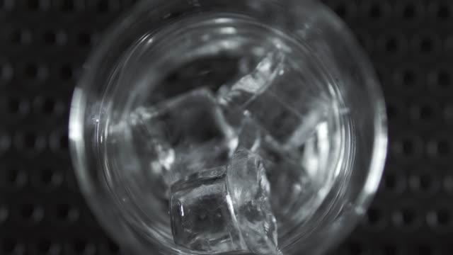 makro bir kadeh kokteyl bardağına düşen ve etrafında döner buz küpleri. kokteyl yapımında. - küp buz stok videoları ve detay görüntü çekimi