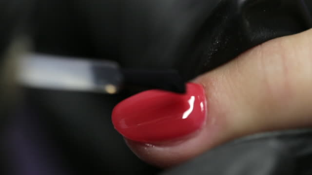 macro shot of master in black gloves painting fingernail her client in red color - ноготь на руке стоковые видео и кадры b-roll