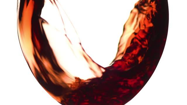 ワイングラスに注ぐ赤ワインまたはローズワインのマクロショット。スローモーション - ワイングラス点の映像素材/bロール