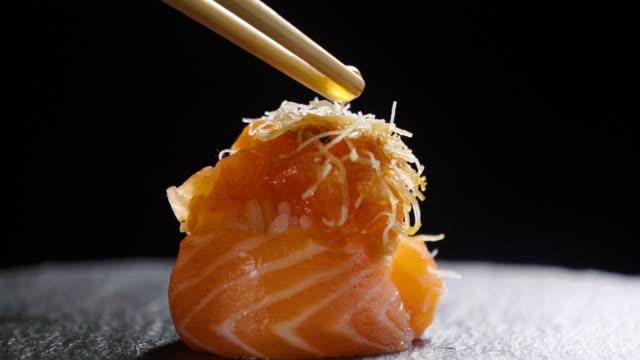 vídeos y material grabado en eventos de stock de tiro de macro de sushi, sashimi, uramaki y nighiri.typical plato japonés que consiste en arroz, salmón o atún, camarón y pescado huevos sobre un fondo negro. - sushi