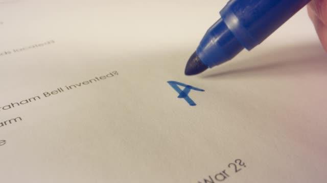 Macro shot of teacher's pen marking a score on a school test