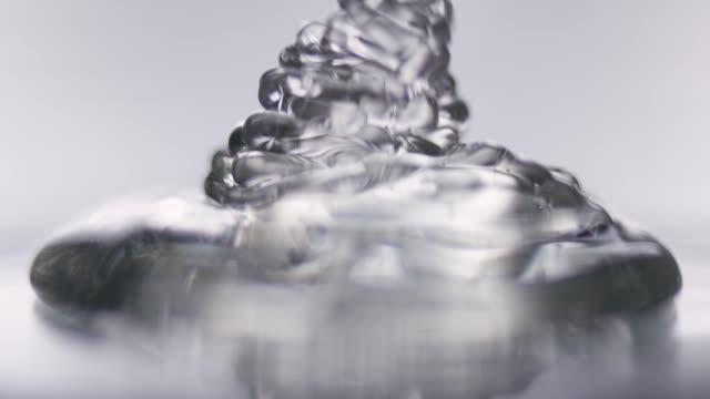 vídeos de stock, filmes e b-roll de tiro macro de gel transparente, acumulando em um plade glas - skincare